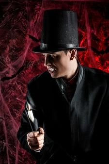 Przystojny mężczyzna ubrany w kostium drakuli na halloween. atrakcyjny wampir ze świecami