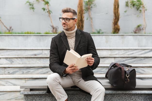 Przystojny mężczyzna ubrany w kurtkę, czytając książkę siedząc na zewnątrz
