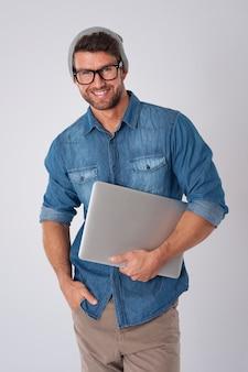 Przystojny mężczyzna ubrany w modne okulary i wełniany kapelusz z laptopem