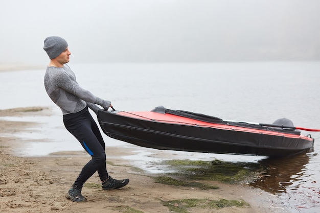 Przystojny mężczyzna ubrany w sportową odzież i czapkę, ciągnąc kajak na brzeg z wody