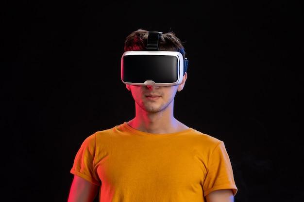 Przystojny mężczyzna ubrany w zestaw słuchawkowy wirtualnej rzeczywistości na ciemnej powierzchni