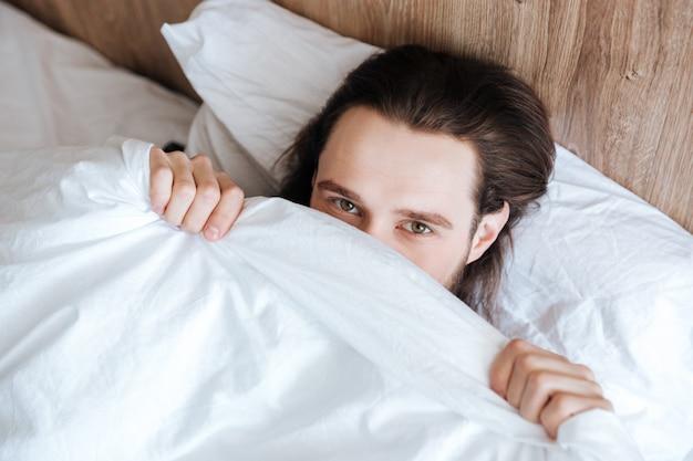 Przystojny mężczyzna ukrywa twarz pod białą narzutą w łóżku