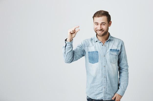 Przystojny mężczyzna uśmiecha się do kamery pokazuje coś małego.