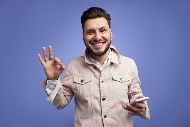 Przystojny mężczyzna uśmiecha się i gestykuluje ok, trzymając telefon komórkowy