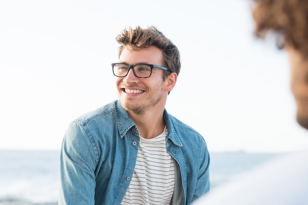 Przystojny mężczyzna uśmiecha się na plaży i odwraca wzrok