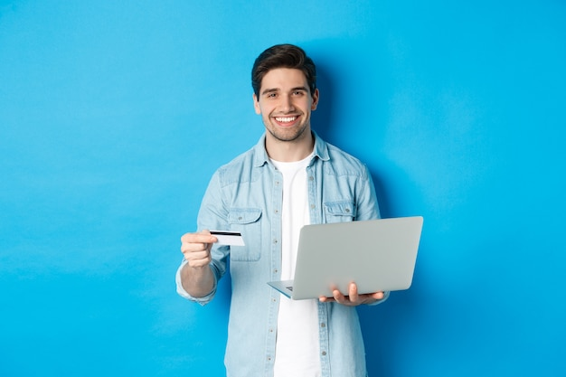 Przystojny mężczyzna uśmiecha się, robi zakupy online i płaci za produkt, trzymając kartę kredytową z laptopem, stojąc na niebieskim tle.