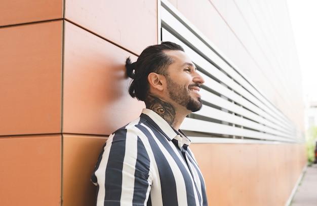 Przystojny mężczyzna uśmiechający się na ścianie na ulicy