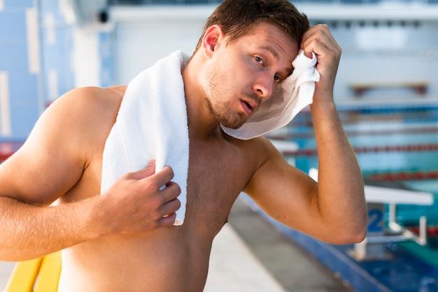 Przystojny mężczyzna używa białego ręcznika
