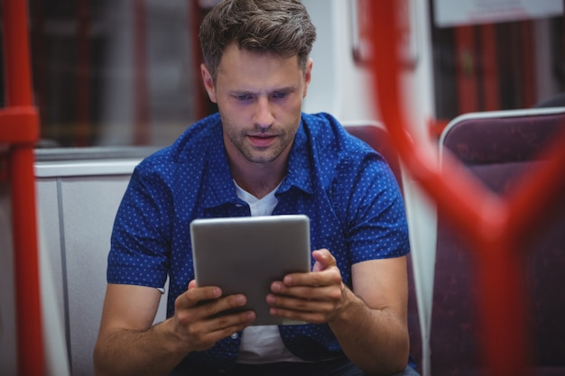 Przystojny mężczyzna używa cyfrową pastylkę w pociągu