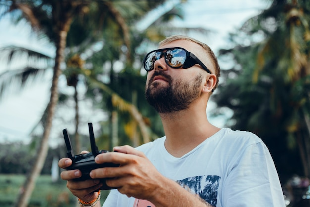 Przystojny mężczyzna używa drona na ulicy