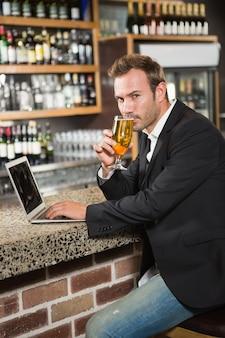 Przystojny mężczyzna używa laptop i pije piwo