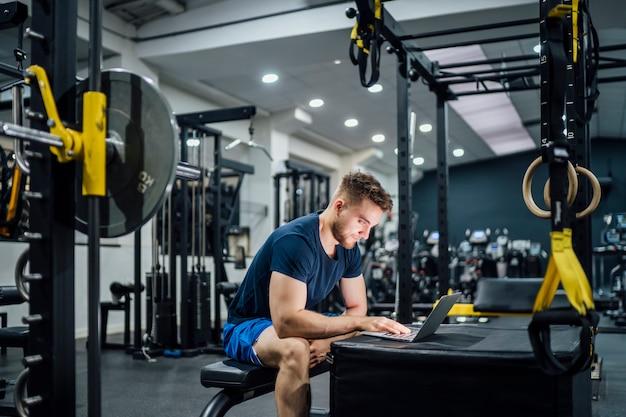 Przystojny mężczyzna używa laptop w gym