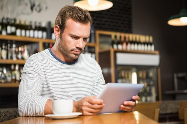 Przystojny mężczyzna używa pastylka komputer