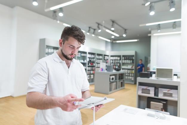 Przystojny mężczyzna używa tabletu w sklepie elektronicznym