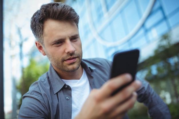 Przystojny mężczyzna używa telefon komórkowego