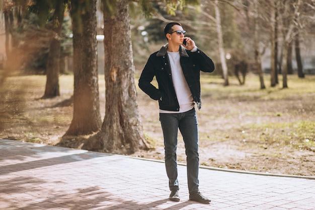 Przystojny mężczyzna używa telefon w parku