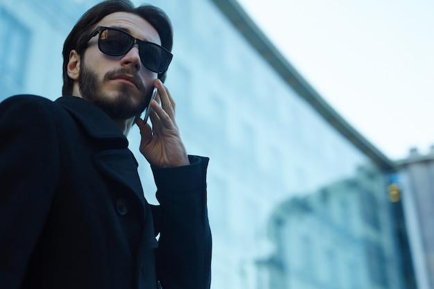 Przystojny mężczyzna używa telefon w ulicach miasto