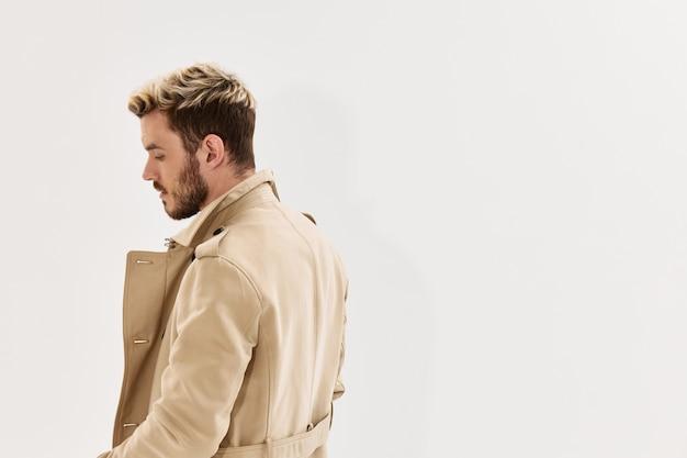 Przystojny mężczyzna w beżowym płaszczu widok z tyłu styl jesień na białym tle