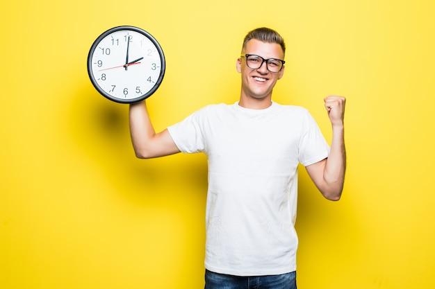 Przystojny mężczyzna w białej koszulce i przezroczystych okularach trzyma w jednej ręce duży zegar