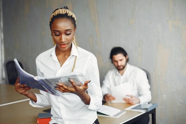 Przystojny mężczyzna w białej koszuli. afrykańska kobieta z partnerem. facet z laptopem.