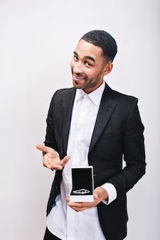 Przystojny mężczyzna w białej koszuli i eleganckiej czarnej kurtce, trzymając prezent biżuterii w rękach i uśmiechnięty. święta, prezent, wesoły nastrój, ozdoby, prawdziwie pozytywne emocje.