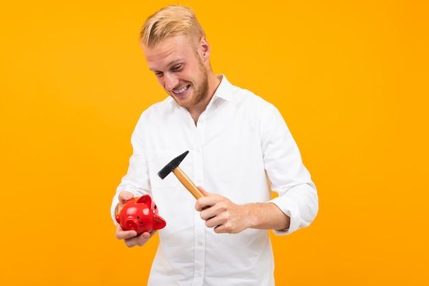 Przystojny mężczyzna w białej koszuli rozbija skarbonkę młotkiem na żółto