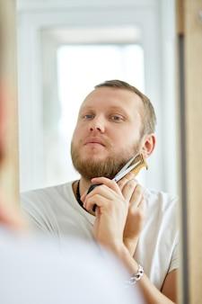 Przystojny mężczyzna w białej koszuli tnącej brodę sam z nożyczkami w domu
