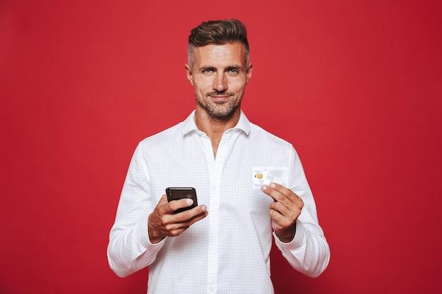 Przystojny mężczyzna w białej koszuli trzymający kartę kredytową i smartfona na czerwonym tle