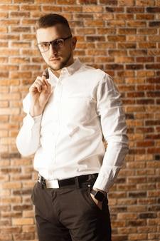 Przystojny mężczyzna w białej koszuli w okularach stojący w pobliżu ściany z czerwonej cegły