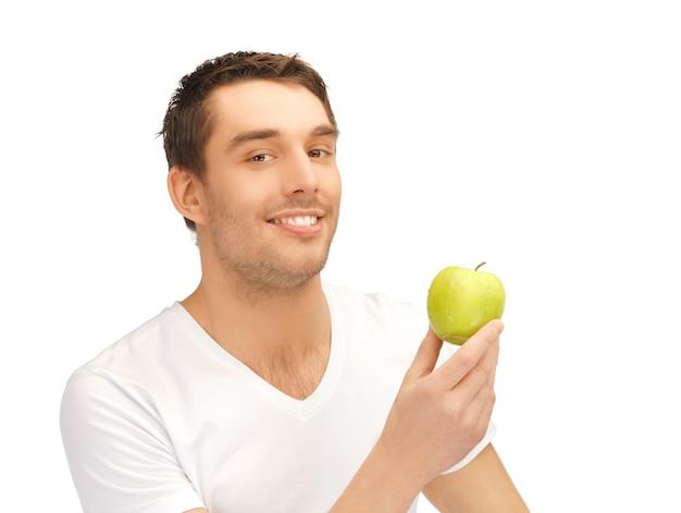 Przystojny mężczyzna w białej koszuli z zielonym jabłkiem