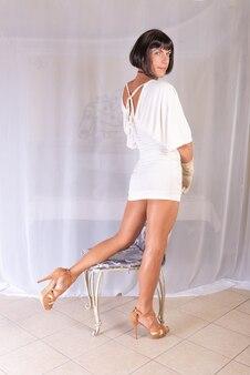 Przystojny mężczyzna w białej sukni stoi plecami i odwraca się