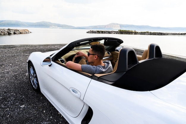 Przystojny mężczyzna w białym samochodzie