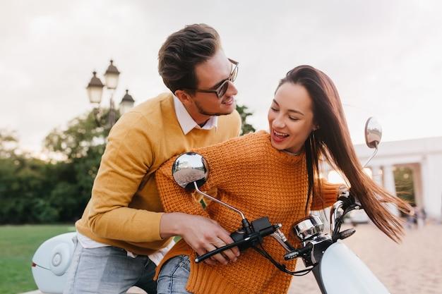 Przystojny mężczyzna w ciemnych okularach przeciwsłonecznych rozmawia z ładną kobietą, podczas gdy ona uczy się jeździć
