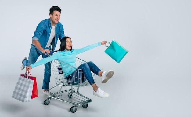 Przystojny mężczyzna w codziennych ubraniach pcha wózek sklepowy z cudowną dziewczyną z kolorowymi papierowymi torebkami w dłoniach.