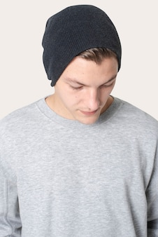 Przystojny mężczyzna w czarnej czapce i szarym swetrze zimowa sesja zdjęciowa w studio odzieży