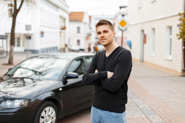 Przystojny mężczyzna w czarnej koszulce w pobliżu samochodu w mieście