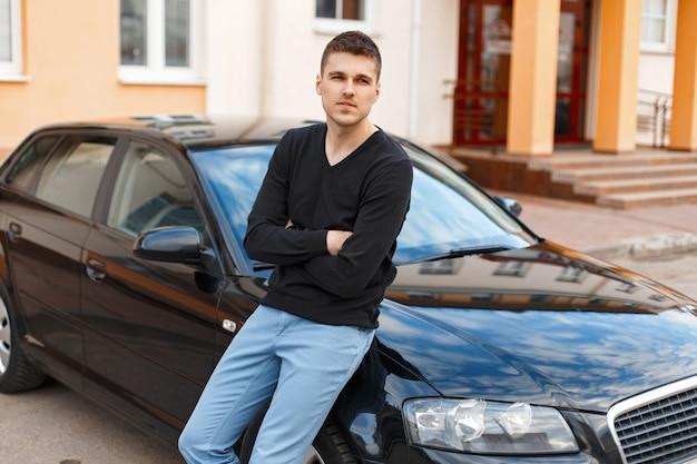 Przystojny mężczyzna w czarnej koszulce w pobliżu samochodu