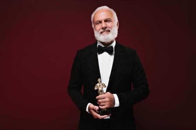 Przystojny mężczyzna w czarnej kurtce trzymający statuetkę oscara
