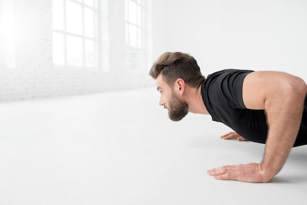 Przystojny mężczyzna w czarnej odzieży sportowej robi pompki w pomieszczeniu w białym wnętrzu siłowni