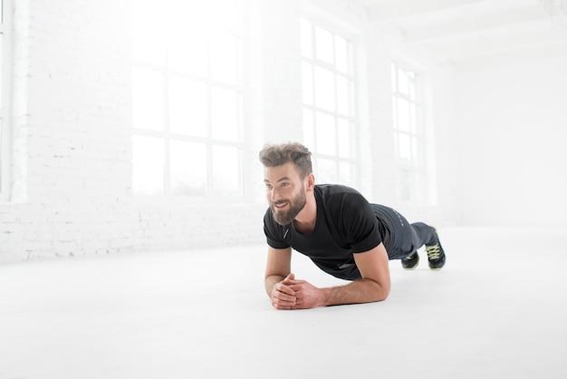 Przystojny mężczyzna w czarnej odzieży sportowej trzyma deskę na podłodze w białym wnętrzu siłowni