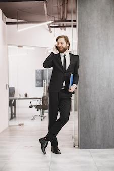 Przystojny mężczyzna w czarnym garniturze. biznesmen z telefonem komórkowym.