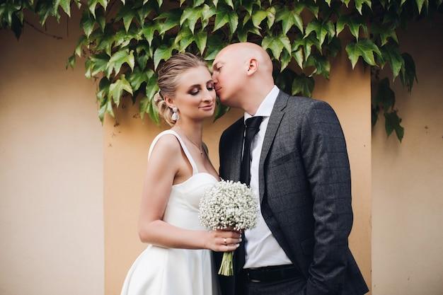 Przystojny mężczyzna w czarnym garniturze i białej koszuli całuje swoją śliczną żonę o jasnych włosach w białej sukni z bukietem białych kwiatów
