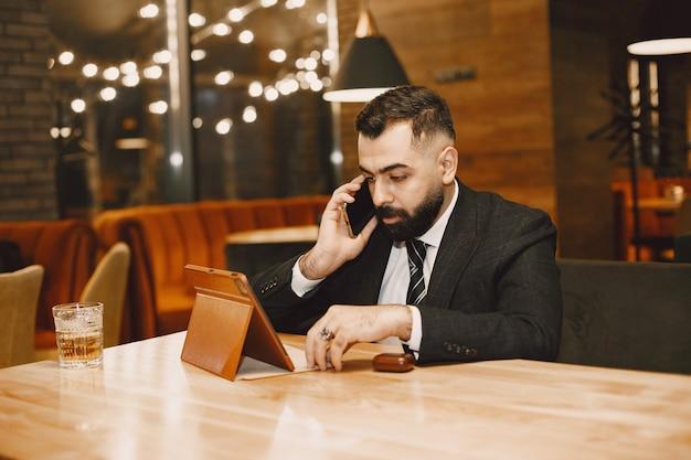 Przystojny mężczyzna w czarnym garniturze, pracujący w kawiarni