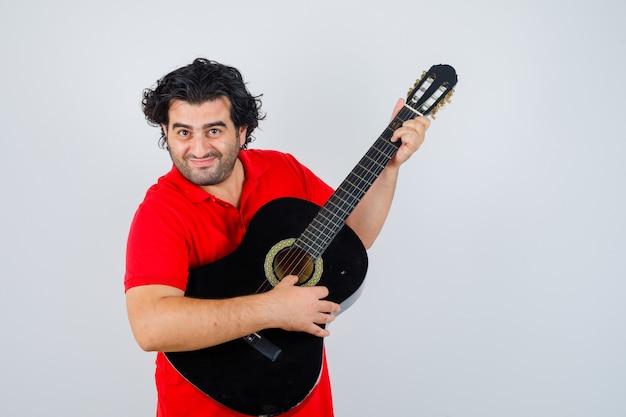 Przystojny mężczyzna w czerwonej koszulce, gra na gitarze i szczęśliwy, widok z przodu.