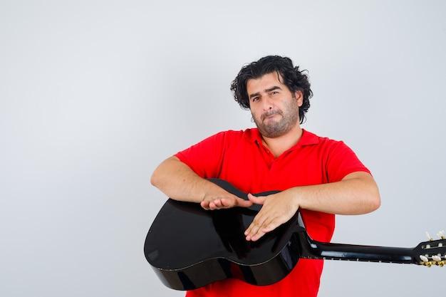 Przystojny mężczyzna w czerwonej koszulce puka na gitarze i patrząc szczęśliwy, przedni widok.