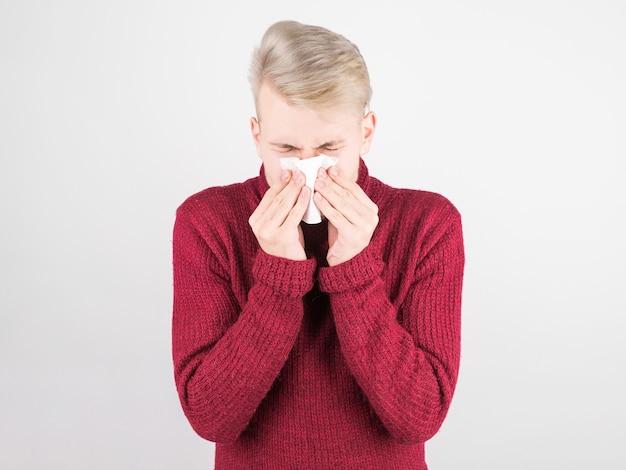 Przystojny mężczyzna w czerwonym szaliku jest przeziębiony i wydmuchuje nos w serwetkę. pojęcie medycyny i sezonowych przeziębień.