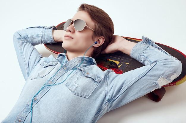 Przystojny mężczyzna w dżinsy kurtkę i okulary przeciwsłoneczne leży na deskorolce