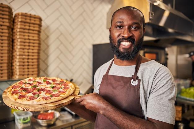 Przystojny mężczyzna w fartuchu patrzący w kamerę i uśmiechający się, trzymając drewnianą deskę z pyszną pizzą