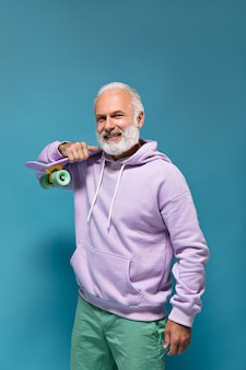 Przystojny mężczyzna w fioletowej bluzie z kapturem trzymający longboard