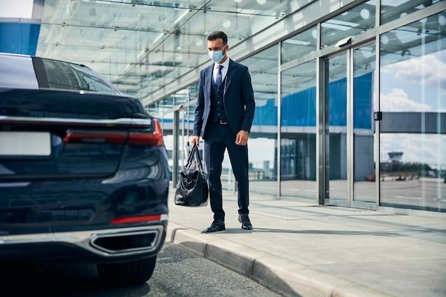 Przystojny mężczyzna w garniturze opuszcza lotnisko i jedzie taksówką z bagażem w ręku